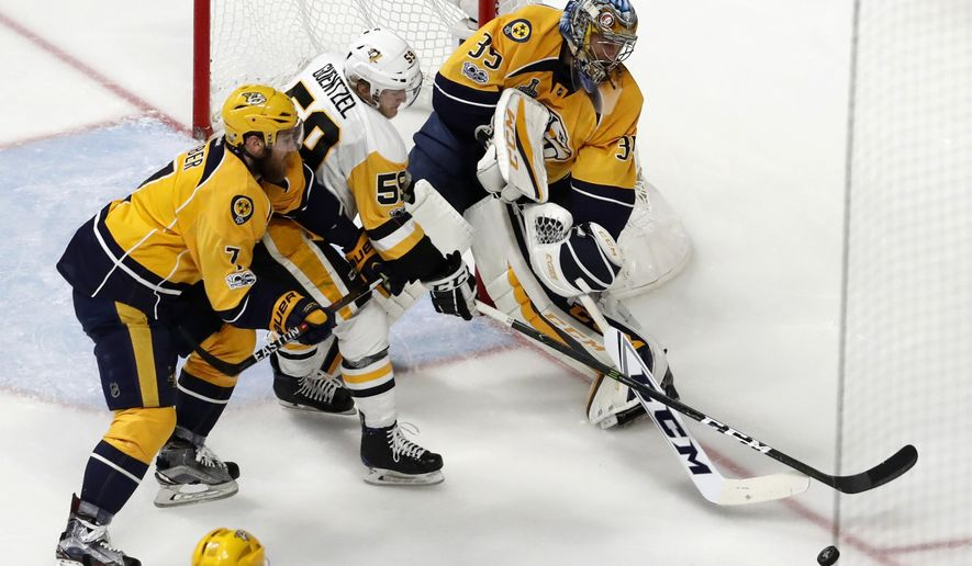 Nashville Predators goalie Pekka Rinne (35), of Finland, and Yannick Weber (7), of Switzerland, defend the goal against Pittsburgh Penguins' Jake Guentzel (59) during the third period of Game 6 of the NHL hockey Stanley Cup Final, Sunday, June 11, 2017, in Nashville, Tenn. (AP Photo/Jeff Roberson)