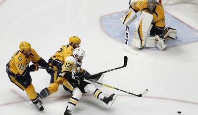 Pittsburgh Penguins' Bryan Rust (17) battles for the puck against Nashville Predators's Cody McLeod (55) and Matt Irwin (52) as Nashville Predators goalie Pekka Rinne (35), of Finland, guards the goal during the second period of Game 6 of the NHL hockey Stanley Cup Final, Sunday, June 11, 2017, in Nashville, Tenn. (AP Photo/Jeff Roberson)