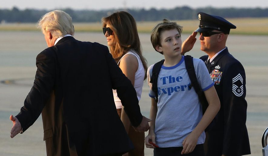 Barron Trump, second from right, son of President Donald Trump, looks back at Air Force One after arriving with the president and first lady Melania Trump at Andrews Air Force Base, Md., Sunday, June 11, 2017. Trump was returning to Washington after spending the weekend at Trump National Golf Club in Bedminster, N.J. (AP Photo/Patrick Semansky)