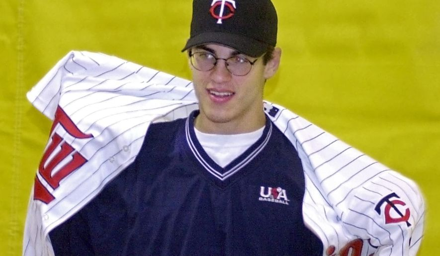 FILE - In this June 5, 2001, file photo, Joe Mauer puts on a Minnesota Twins jersey during a news conference at his high school in St. Paul, Minn., after he became the No. 1 overall pick in the Major League amateur draft. The Twins have the No. 1 pick in the MLB draft for the first time since 2001. Back then, they took a chance on Mauer, a hometown kid, over can't-miss prospect Mark Prior. (AP Photo/Jim Mone, File)