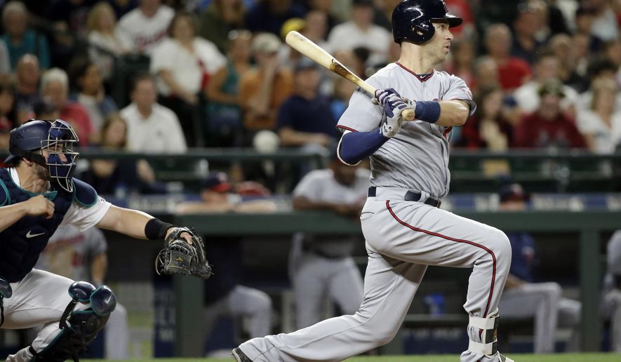 FILE - In this Wednesday, June 7, 2017, file photo, Minnesota Twins' Joe Mauer watches the path of his RBIn single as Seattle Mariners catcher Mike Zunino looks on in the fifth inning of a baseball game in Seattle. The Twins have the No. 1 pick in the MLB draft for the first time since 2001. Back then, they took a chance on Mauer, a hometown kid, over can't-miss prospect Mark Prior. (AP Photo/Elaine Thompson, File)