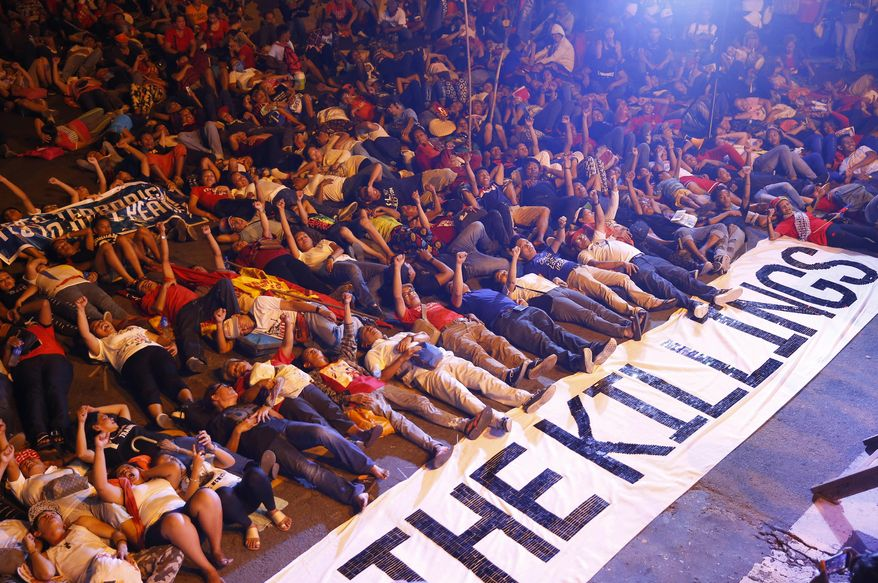 """Protesters stage die-in with a banner reading """"Stop the killings"""" during a rally near the Presidential Palace to denounce the Martial Law declaration of President Rodrigo Duterte after Muslim militants laid a siege of Marawi city in southern Philippines for three weeks, Monday, June 12, 2017 in Manila, Philippines. The protesters also denounced the killings by Duterte's bloody anti-drug crackdown. (AP Photo/Bullit Marquez)"""