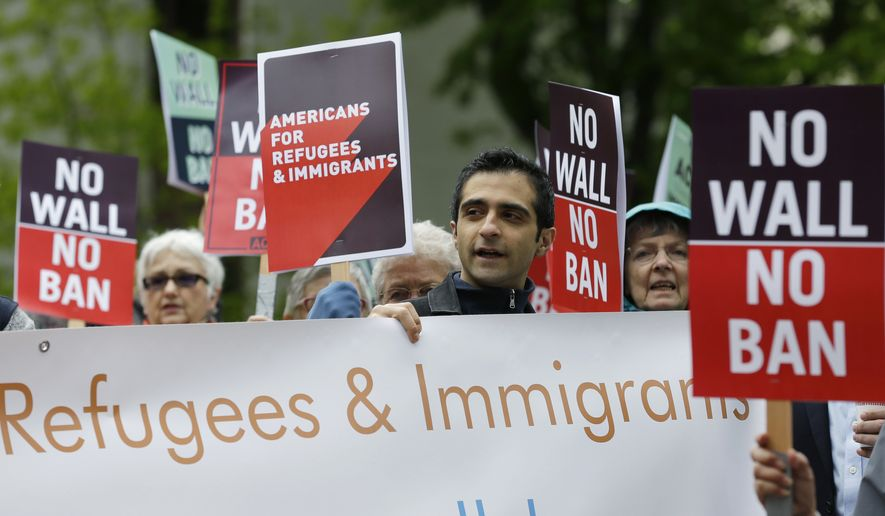 In this May 15, 2017, file photo, protesters hold signs during a demonstration against President Donald Trump's revised travel ban, Monday, May 15, 2017, outside a federal courthouse in Seattle. A three-judge panel of the 9th U.S. Circuit Court of Appeals on Monday upheld a decision to block the revised travel ban, which would suspend the nation's refugee program and temporarily bar new visas for citizens of Iran, Libya, Somalia, Sudan, Syria and Yemen. (AP Photo/Ted S. Warren, file)
