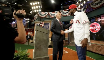 Jordon Adell, right, an outfielder and pitcher from Ballard High School in Louisville, Ky., shakes hands with commissioner Rob Manfred after being selected No. 10 by the Los Angeles Angels in the first round of the Major League Baseball draft, Monday, June 12, 2017, in Secaucus, N.J. (AP Photo/Julio Cortez)