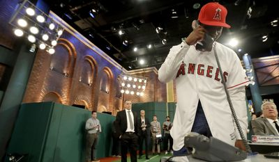 Jordon Adell, an outfielder and pitcher from Ballard High School in Louisville, Ky., talks to a member of the Los Angeles Angels after being selected No. 10 by the Angels in the first round of the Major League Baseball draft, Monday, June 12, 2017, in Secaucus, N.J. (AP Photo/Julio Cortez)