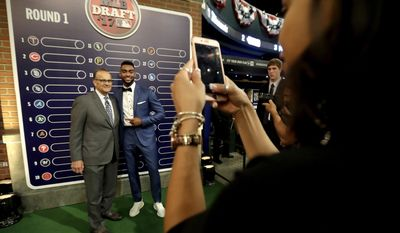 Jordon Adell, center, an outfielder and pitcher from Ballard High School in Louisville, Ky., poses for a photograph with former New York Yankees manager Joe Torre, left, prior to the Major League Baseball draft, Monday, June 12, 2017, in Secaucus, N.J.(AP Photo/Julio Cortez)
