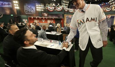 Trevor Rogers, a pitcher from Carlsbad High School in Carlsbad, N.M., right, shakes hands with former New York Yankees player Nick Swisher after being selected No. 13 by the Miami Marlins in the first round of the Major League Baseball draft, Monday, June 12, 2017, in Secaucus, N.J. (AP Photo/Julio Cortez)