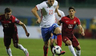 FILE - In this Saturday, Nov. 14, 2015 filer, Russia's Artyom Dzyuba, front, fights for the ball with Portugal's Gonsalo Guedes, right, and Cedric Soares during an international friendly soccer match between Russia and Portugal in Krasnodar, Russia. (AP Photo/Alexandr Mysyakin, File)