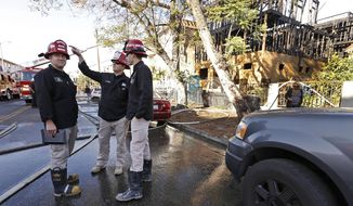 LA City Fire arson investigators at the scene in the 400 block of Heliotrope Drive in East Hollywood Monday, June 12, 2017, after a fire heavily damaged an apartment building under construction and also damaged an adjacent apartment building, a garage and a house. Firefighters extinguished the flames in about 45 minutes with 1 minor injury to a firefighter. A suspect who may have set the fires is in custody.   (Al Seib /Los Angeles Times via AP)