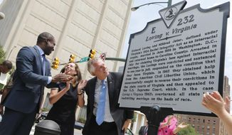 CORRECTS FIRST NAME TO LEVAR- Virginia Gov. Terry McAuliffe , right, looks over a historical marker, along with his wife, Dorothy, center, and Richmond Mayor Levar Stoney, left, that was unveiled commemorating the 50th anniversary of the U.S. Supreme Court decision that struck down bans on interracial marriage Monday, June 12, 2017, in Richmond, Va. The new historical marker to commemorate the lawsuit brought by Richard and Mildred Loving, was dedicated outside the old Virginia Supreme Court, which ruled against the Lovings before they ultimately won in the U.S. Supreme Court. (AP Photo/Steve Helber)