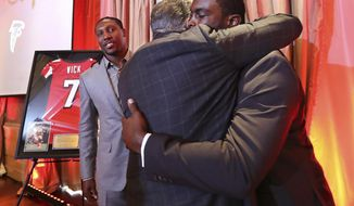 Former Atlanta Falcons quarterback Michael Vick hugs owner Arthur Blank with wide receiver Roddy White looking on as the Atlanta Falcons honor Vick and White as they officially retire from the NFL on Monday, June 12, 2017, in Atlanta. (Curtis Compton/Atlanta Journal-Constitution via AP)
