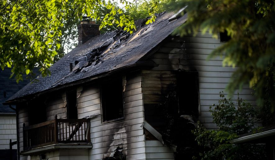 Michigan State Police fire investigators work to find the cause of an early morning blaze that claimed three lives on Monday, June 12, 2017, in Flint, Mich.  (Jake May /The Flint Journal-MLive.com via AP)