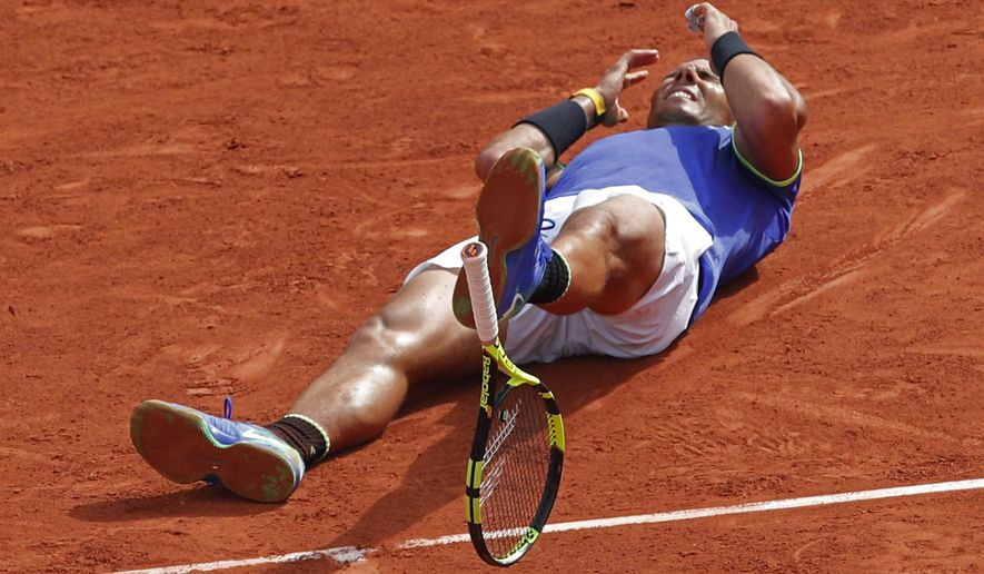 Spain's Rafael Nadal's racket falls on the clay as he celebrates winning his tenth French Open title against Switzerland's Stan Wawrinka in three sets, 6-2, 6-3, 6-1, during their men's final match of the French Open tennis tournament at the Roland Garros stadium, in Paris, France, Sunday, June 11, 2017. (AP Photo/Christophe Ena)