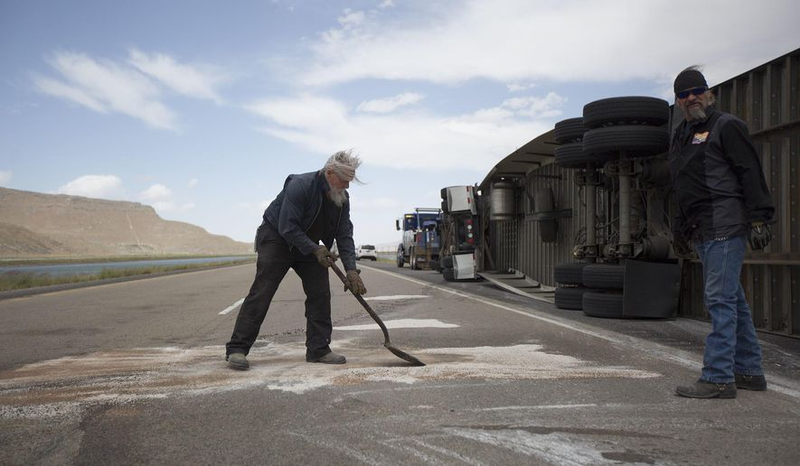 Bob Williams and Kenny Phillips clean the road after four semi-trucks blew over off of Interstate 80 near, Dugway, Utah Monday, June 12, 2017. (Kelsey Brunner/The Deseret News via AP)