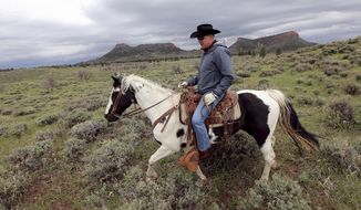 FILE - In this May 9, 2017, file photo, Interior Secretary Ryan Zinke rides a horse in the new Bears Ears National Monument near Blanding, Utah. Zinke on Monday, June 12, 2017, recommended that the new national monument in Utah be reduced in size and said Congress should step in to designate how selected areas of the 1.3 million-acre site are managed. (Scott G Winterton/The Deseret News via AP, File)