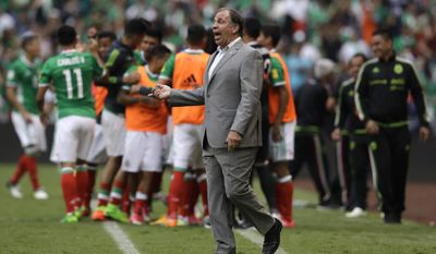 United States coach Bruce Arena gives instructions to his players as Mexico's Carlos Vela, 11, celebrates with teammates after scoring his team's first goal against the U.S. during their World Cup soccer qualifying match at Azteca Stadium in Mexico City, Sunday, June 11, 2017.(AP Photo/Rebecca Blackwell)