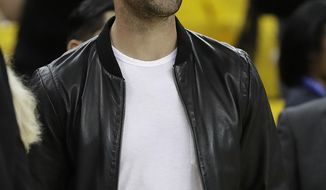 Green Bay Packers quarterback Aaron Rodgers watches as players warm up before Game 5 of basketball's NBA Finals between the Golden State Warriors and the Cleveland Cavaliers in Oakland, Calif., Monday, June 12, 2017. (AP Photo/Marcio Jose Sanchez)