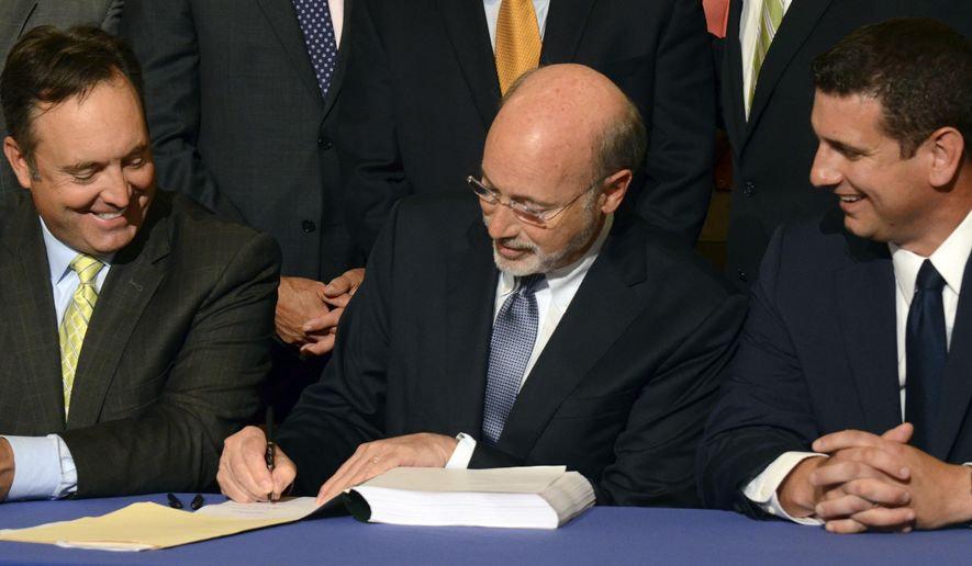 Democratic Gov. Tom Wolf signs legislation designed to reduce long-term public pension costs during a signing ceremony in the Pennsylvania Capitol on Monday, June 12, 2017 in Harrisburg, Pa. Looking on are Senate Majority Leader Jake Corman, R-Centre, left, and House Majority Leader Dave Reed, R-Indiana. (AP Photo/Marc Levy)