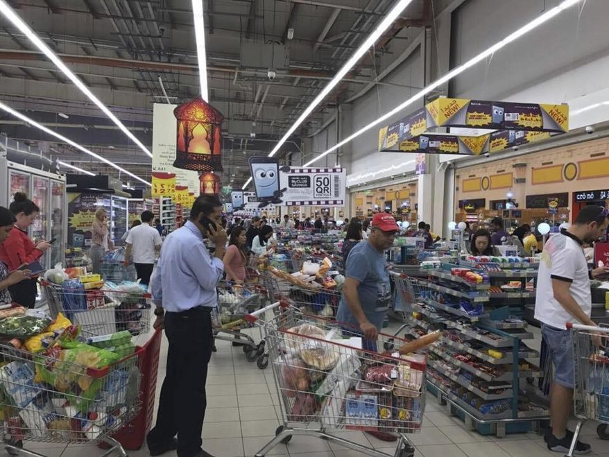 FILE -- In this Monday, June 5, 2017 file photo, provided by Doha News, shoppers stock up on supplies at a supermarket in Doha, Qatar after Saudi Arabia closed its land border with Qatar, through which the tiny Gulf nation imports most of its food. Qatar said Monday, June 12, 2017, that it had begun shipping cargo through Oman to bypass Gulf countries that have cut off sea and land routes to the tiny, energy-rich nation, the latest move by Doha to show it can survive a diplomatic dispute with its neighbors. (Doha News via AP, File)