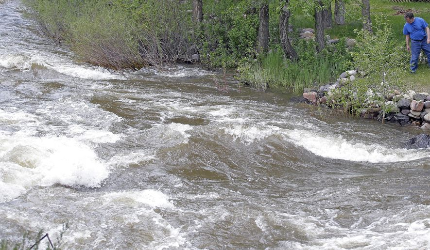 FILE - This Wednesday, May 31, 2017, file photo, Ron Lenfield watches the fast-flowing Weber River along his property, in Oakley, Utah. Rivers in Utah are expected to remain dangerously swollen with icy mountain runoff for several more weeks. (AP Photo/Rick Bowmer, File)