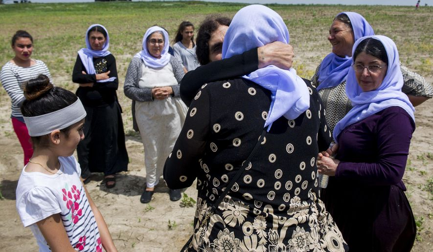 In this July 10, 2017 photo, Basee Naser and Naam Joko embrace each other at the opening ceremony for the future Yazidi Cemetary in Malcolm, Neb. The land was bought for $150,500 in October by the United Yezidi Community of America, a Lincoln nonprofit aiming to unify the Yazidi community. (Amber Baesler/The Journal-Star via AP)