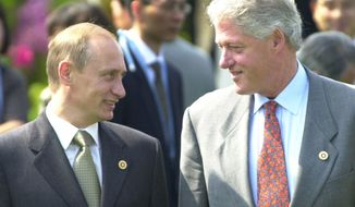 FILE - In this July 21, 2000 file photo, President Bill Clinton shares a light moment with Russian President Vladimir Putin before a Group of Eight meeting in Nago, Okinawa, Japan. In a series of interviews with American film director Oliver Stone being shown on U.S. television on Monday, June 12, 2017, Putin said that he inquired about Russia joining NATO when Clinton visited Moscow in 2000. (AP Photo/Vincent Yu, File)