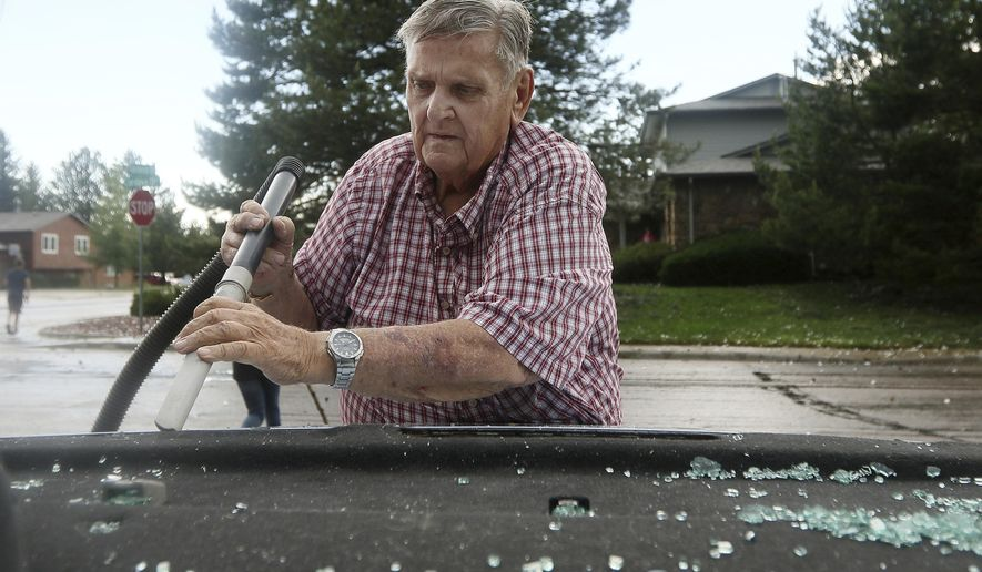 Bill Jones vacuums out the shattered glass from the back window of his granddaughters vehicle at the intersection of Gardenia Drive and Cordova Drive on Monday, June 12, 2017, near Carpenter, Wyo. Severe storms spawned tornadoes and dropped large hail in parts of eastern Wyoming, injuring at least one person. (Blaine McCartney/The Wyoming Tribune Eagle via AP)