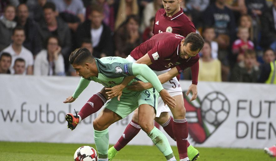 Latvia's Olegs Laizans, right, and Portugal's Andre Silva fight for the ball during their World Cup Group B qualifying match between Latvia and Portugal at the Skonto Stadium in Riga, Latvia, Friday, June 9, 2017. (AP Photo/Roman Koksarov)