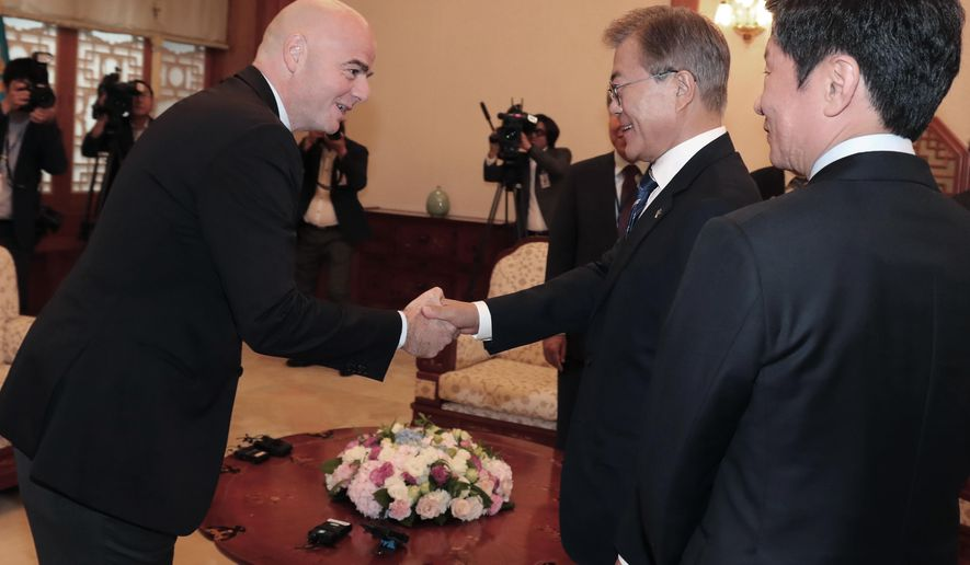 South Korean President Moon Jae-in, center, shakes hands with FIFA President Gianni Infantino during their meeting at the presidential Blue House in Seoul, South Korea, Monday, June 12, 2017. South Korea's new liberal president has proposed that the rival Koreas and other Northeast Asian countries co-host the 2030 World Cup. (Bae Jae-man/Yonhap via AP)