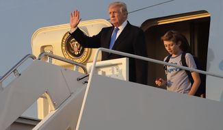President Donald Trump waves in front of his son Barron as he steps off Air Force One after arriving at Andrews Air Force Base, Md., Sunday, June 11, 2017. Trump was returning to Washington after spending the weekend at Trump National Golf Club in Bedminster, N.J. (AP Photo/Patrick Semansky)