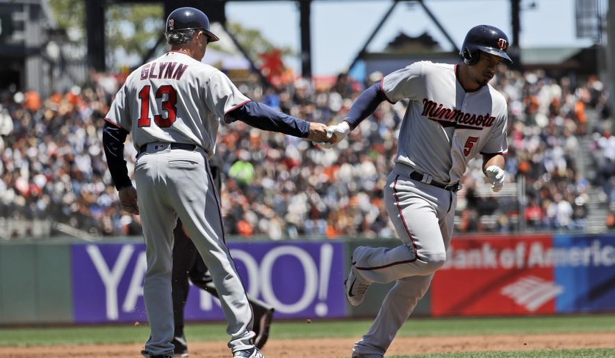 Minnesota Twins' Eduardo Escobar, right, shakes hands with third base coach Gene Glynn (13) after hitting a solo home run against the San Francisco Giants during the second inning of a baseball game Sunday, June 11, 2017, in San Francisco. (AP Photo/Marcio Jose Sanchez)
