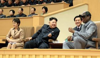 In this Jan. 8, 2014, photo provided by the North Korean government, North Korean leader Kim Jong-un, center, talks with former NBA player Dennis Rodman, right, as they watch an exhibition basketball game at an indoor stadium in Pyongyang. (Korean Central News Agency/Korea News Service via AP)