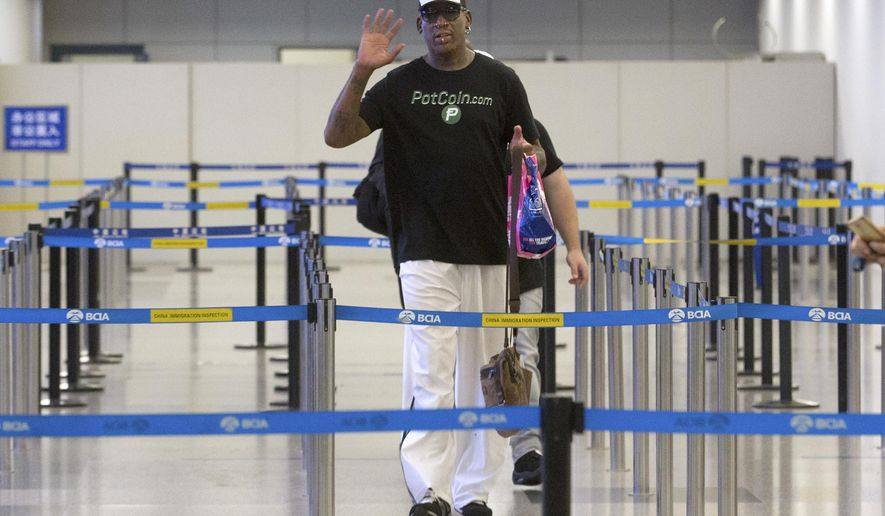 Former NBA basketball player Dennis Rodman gestures to photographers as he prepares to go through immigration at Beijing Capital International Airport in Beijing, Tuesday, June 13, 2017. North Korea is expecting another visit by Rodman on Tuesday in what would be his first to the country since President Donald Trump took office. (AP Photo/Mark Schiefelbein)
