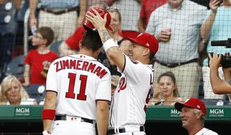 Washington Nationals' Jose Lobaton (59) removes the helmet from the head ofRyan Zimmerman (11) after Zimmerman hit a solo home run during the first inning of the team's baseball game against the Atlanta Braves at Nationals Park, Tuesday, June 13, 2017, in Washington. (AP Photo/Carolyn Kaster)