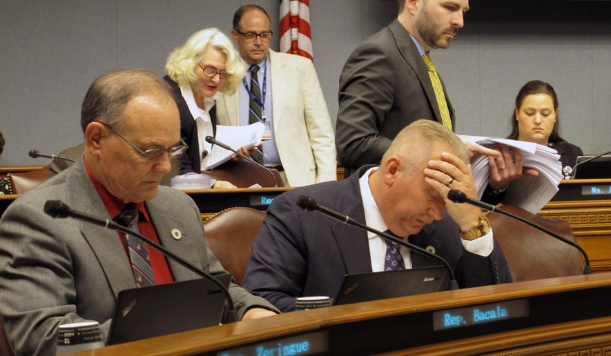 Representatives Tony Bacala, R-Prairieville, left, and Jack McFarland, R-Winnfield, look through the latest House budget proposal as Appropriations Committee staff passes out spreadsheets on Tuesday, June 13, 2017, in Baton Rouge, La. (AP Photo/Melinda Deslatte)