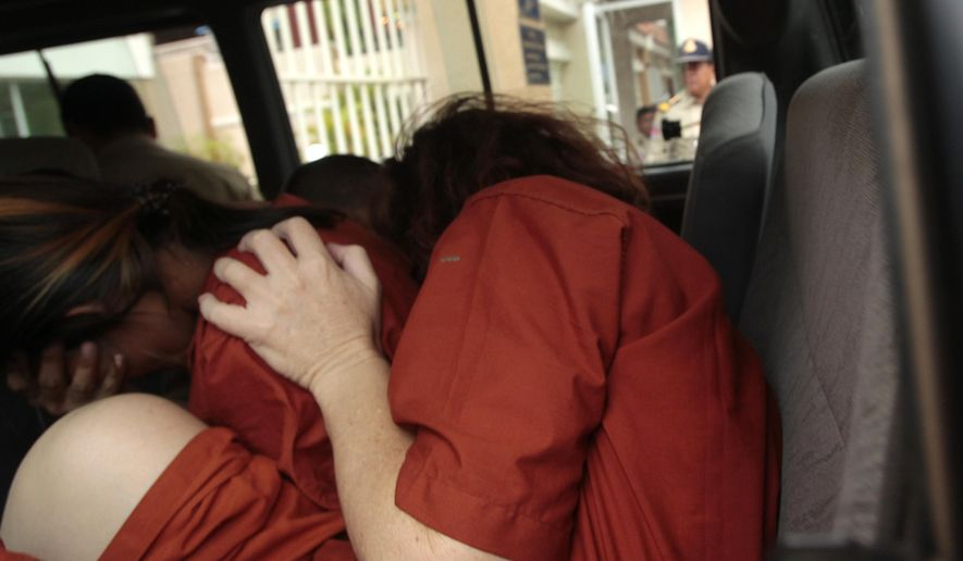 Tammy Davis-Charles, front, charged with providing commercial surrogacy services, hides her face as she is transported to the Phnom Penh Municipal Court in Phnom Penh, Cambodia, Tuesday, June 13, 2017. The Australian Davis -Charles, who is charged with providing commercial surrogacy services in Cambodia, said Tuesday she launched her business only after consulting three local lawyers who assured her that her clinic was legal. (AP Photo/Heng Sinith)