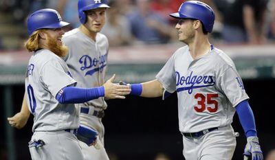Los Angeles Dodgers' Cody Bellinger, right, is congratulated by Justin Turner, left, as Corey Seager, back, watches during the ninth inning of the team's baseball game against the Cleveland Indians, Tuesday, June 13, 2017, in Cleveland. Bellinger hit a three-run home run off Indians relief pitcher Boone Logan. Turner and Seager scored on the play. (AP Photo/Tony Dejak)