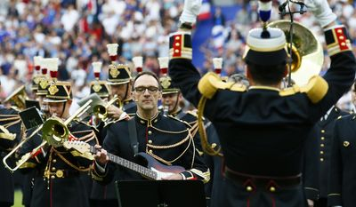 """A member of the Republican Guard plays guitar while singing """"Don't Look Back in Anger"""" from Oasis before a friendly soccer match between France and England at the Stade de France in Saint Denis, north of Paris, France, Tuesday, June 13, 2017. After their talks at the Elysee Palace, Fench President Emmanuel Macron and Britain's Prime Minister Theresa May watch a France-England football match that will honor victims of extremist attacks in both countries. (AP Photo/Francois Mori"""