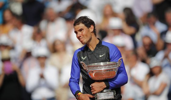 An emotional Rafael Nadal of Spain holds the trophy as he celebrates winning his tenth French Open title against Switzerland's Stan Wawrinka in three sets, 6-2, 6-3, 6-1, during their men's final match of the French Open tennis tournament at the Roland Garros stadium, in Paris, France, Sunday, June 11, 2017. (AP Photo/Christophe Ena)