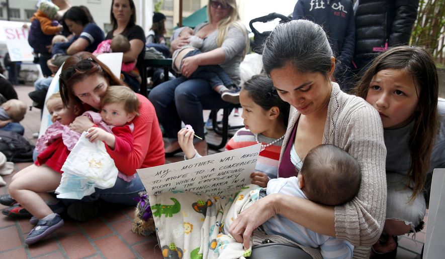 In this March 30, 2016 photo, Mildred Musni, right, breast feeds her son Eliseo and is joined by other mothers in protest at the main entrance of the city Human Services Agency in San Francisco. Months before the protest, Musni was forced to cover up by a security guard when she attempted to feed Eliseo inside the facility. With Musni are her older daughter Sentia, left, and step-daughter Vanessa Trujillo, right. Every employer in San Francisco will have to provide a safe and clean room with a surface, chair and electrical outlet where new moms can pump milk under a proposal pending before city supervisors Tuesday, June 13, 2017. (Paul Chinn/San Francisco Chronicle via AP)