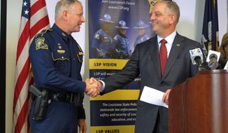 Gov. John Bel Edwards congratulates Col. Kevin Reeves, left, after announcing Reeves as the permanent superintendent of the Louisiana State Police, on Tuesday, June 13, 2017, in Baton Rouge, La. Reeves had worked in the position as interim superintendent. (AP Photo/Melinda Deslatte)