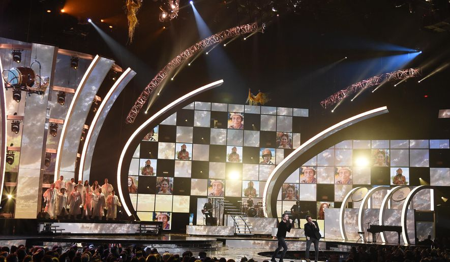 """FILE - In this Nov. 17, 2016 file photo, Juanes, center left, and Pablo Lopez perform """"Tu Enemigo"""" with the cast members from Cirque du Soleil """"Mystere"""" at the 17th annual Latin Grammy Awards in Las Vegas. The nominees for the 2017 Latin Grammy Awards will be announced on Sept. 20, 2017, and the awards will be handed out on Nov. 16. The 18th annual Latin Grammy Awards will air live on Univision from the MGM Grand Garden Arena in Las Vegas.  (Photo by Chris Pizzello/Invision/AP, FIle)"""