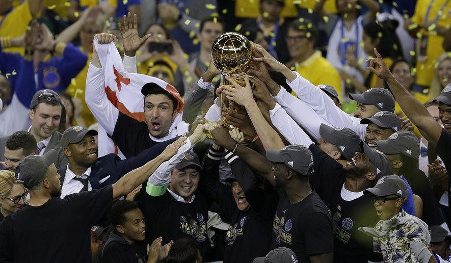 Golden State Warriors players, coaches and owners hold up the Larry O'Brien NBA Championship Trophy after Game 5 of basketball's NBA Finals between the Warriors and the Cleveland Cavaliers in Oakland, Calif., Monday, June 12, 2017. The Warriors won 129-120 to win the NBA championship. (AP Photo/Ben Margot)