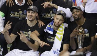 Golden State Warriors guard Klay Thompson, from left, guard Stephen Curry and forward Kevin Durant celebrate after Game 5 of basketball's NBA Finals against the Cleveland Cavaliers in Oakland, Calif., Monday, June 12, 2017. The Warriors won 129-120 to win the NBA championship. (AP Photo/Marcio Jose Sanchez)