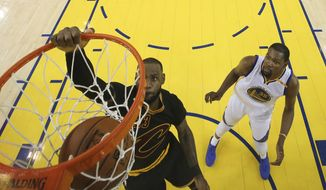 Cleveland Cavaliers forward LeBron James, left, dunks in front of Golden State Warriors forward Kevin Durant (35) during the second half of Game 5 of basketball's NBA Finals in Oakland, Calif., Monday, June 12, 2017. The Warriors won 129-120 to win the NBA championship. (Ezra Shaw/Pool Photo via AP)