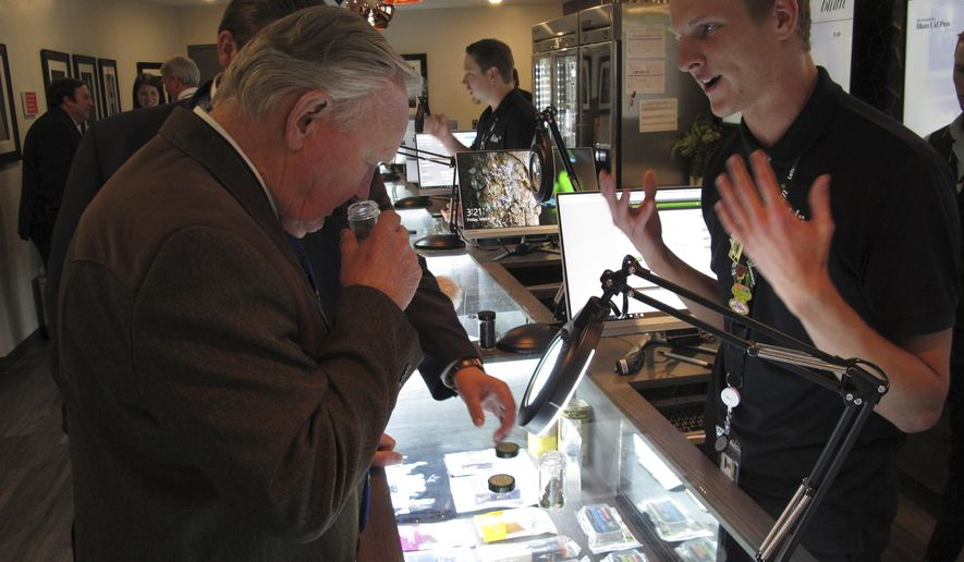 In this March 24, 2017, file photo, Nevada state Sen. Don Gustavson, R-Sparks, smells a sample of marijuana as Christopher Price, a ''budtender'' at the Blum medical marijuana dispensary, describes the operation during a brief tour a the store in Reno, Nev. A judge in Nevada is trying to decide whether the state's first sales of recreational marijuana should begin as scheduled July 1 despite complaints from alcohol distributors. Lawyers for the liquor distributors and the Nevada Department of Taxation go before Judge James Wilson in Carson City Tuesday, June 13, 2017, to argue the case. (AP Photo/Scott Sonner, File)