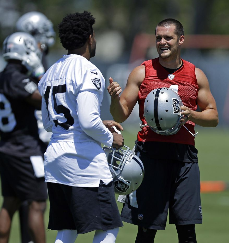Oakland Raiders quarterback Derek Carr, right, speaks with wide receiver Michael Crabtree (15) during NFL football practice on Tuesday, June 13, 2017, at the team's training facility in Alameda, Calif. (AP Photo/Ben Margot)