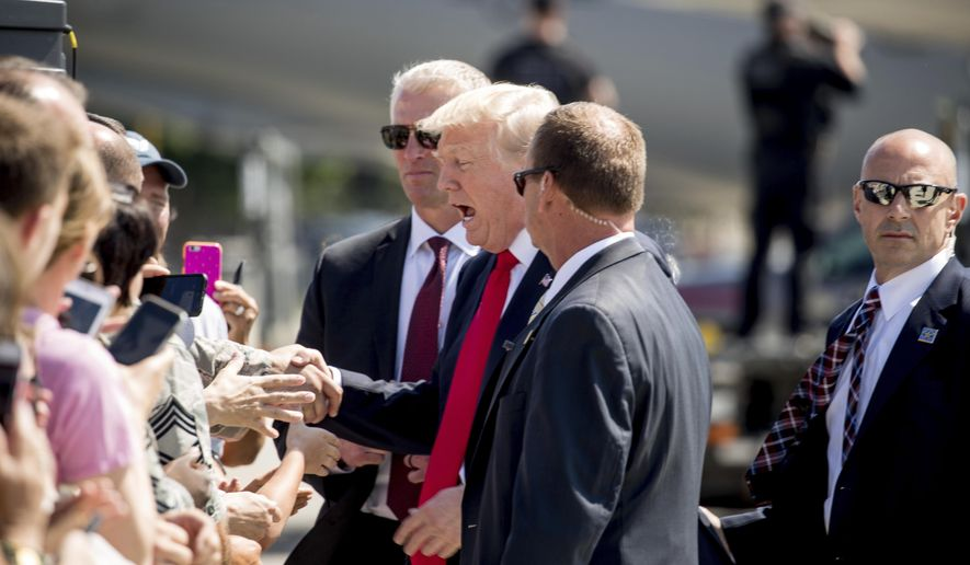 President Donald Trump greets guests on the tarmac after he arrived on Air Force One at General Mitchell International Airport in Milwaukee, Wis., Tuesday, June 13, 2017. (AP Photo/Andrew Harnik)