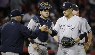 New York Yankees starting pitcher Masahiro Tanaka, right, of Japan, hands the ball to manager Joe Girardi during the seventh inning of a baseball game against the Los Angeles Angels, Monday, June 12, 2017, in Anaheim, Calif. (AP Photo/Jae C. Hong)