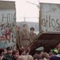 On Nov. 11, 1989, East German border guards are seen through a gap in the Berlin Wall after demonstrators pulled down a segment of the wall at the Brandenburg Gate, Berlin. (Associated Press) ** FILE **